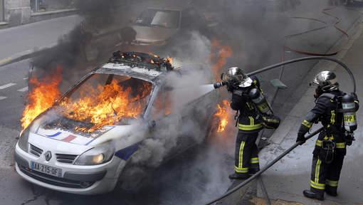 Une voiture de police incendiée par des manifestants à Paris