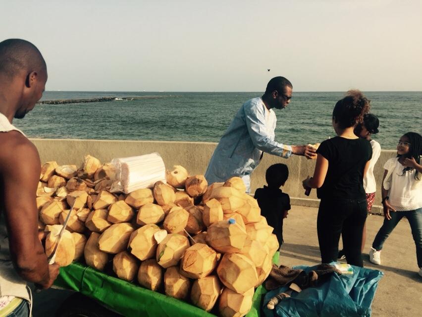 Youssou Ndour et ses enfants en train de boire l'eau de coco non loin de l'embarcadère de Gorée
