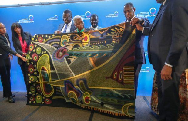 Le Président Macky Sall offrant une œuvre des Manufactures des Arts Décoratifs de Thies « Afrique » à Mme Diop
